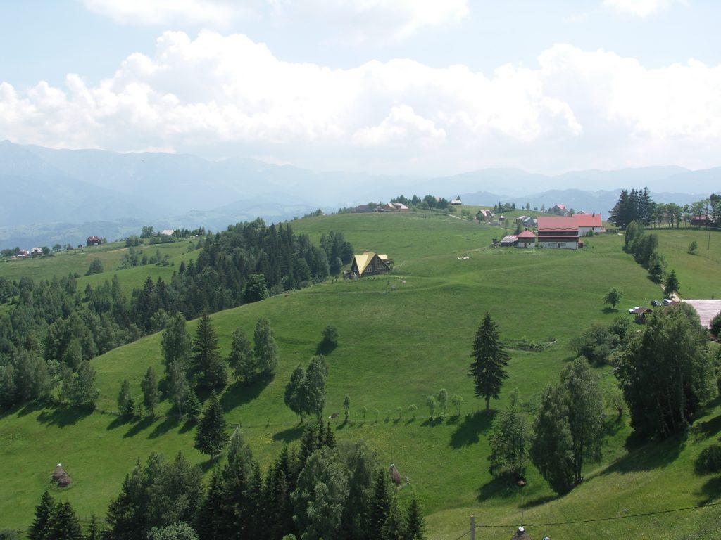 Blue sky, green hills & mountain village view